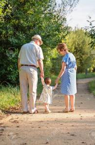 31541115-back-view-of-grandparents-and-baby-grandchild-walking-on-a-nature-path